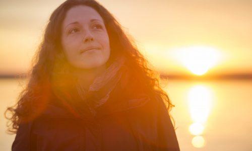 Beautiful young woman enjoying the beautiful sunset at the sea.